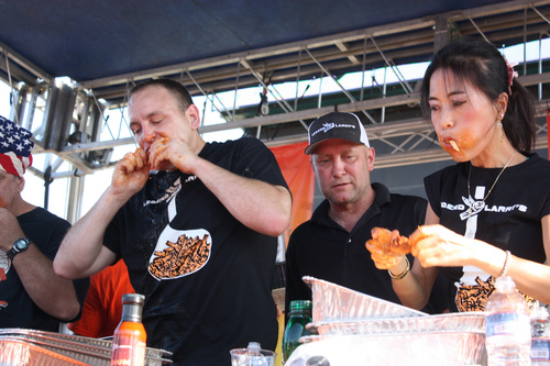 joey chestnut eating alongside sonya thomas at the buffalo wing competition