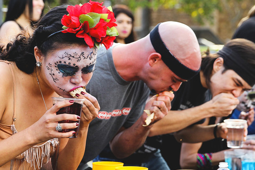 Woman with a skull painted on her face competes in Chacho's taco eating contest next to other competitors including Matthew Stonie.