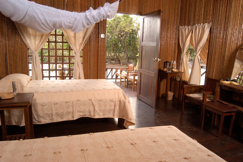 Bedroom with twin beds in bamboo lined hotel room