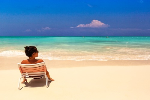 A woman reclines and takes in the sea view at Grace Bay Beach in Providenciales