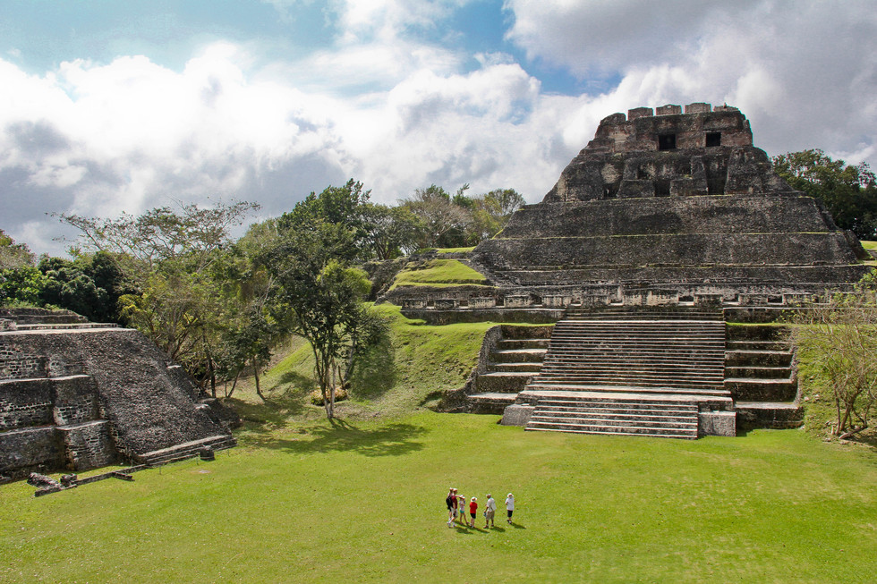 Visitors gaze up at one of the temples of Xunantunich in Belize.