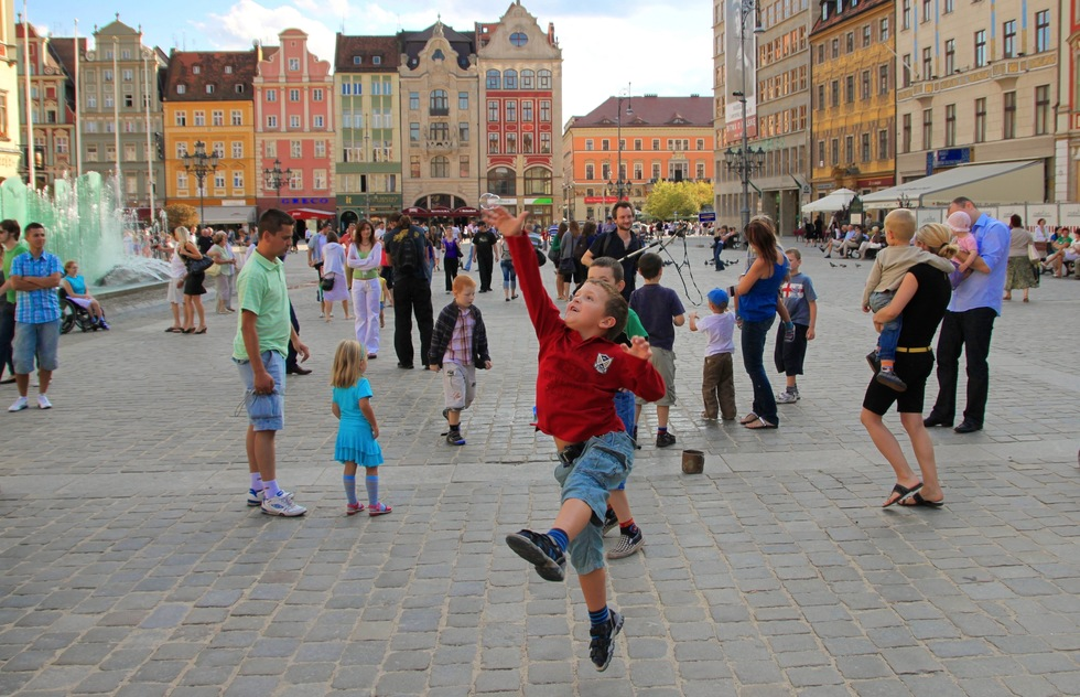 A boy tries to catch a soap bubble in the rynek (market square) of Wroclaw, Poland