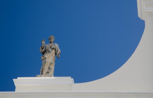 A statue on top of the San Juan Catedral, sillhoueted against the sky.