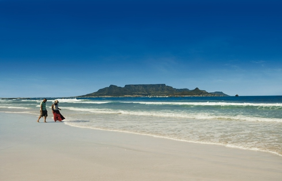 A couple walks along Blouberg Beach in Cape Town, with Table Mountain in the background