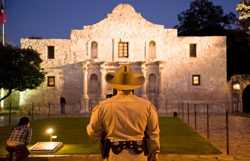 A sheriff stands in front of the Alamo in San Antonio