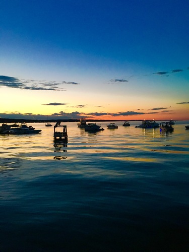 The sun sets on boats in Traverse Bay.