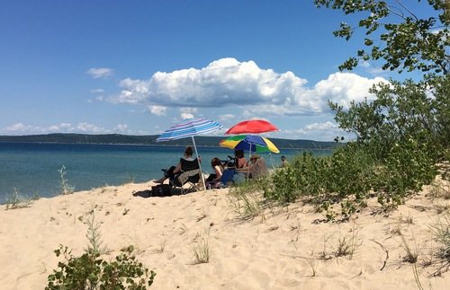 Vacationers sit under colorful beach umbrellas on the beach at Mission Point Park.