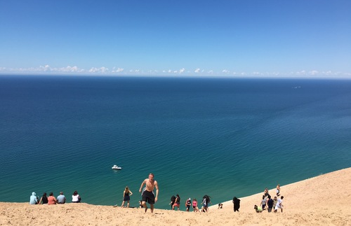 People climbing Sleeping Bear Dunes next to Lake Michigan