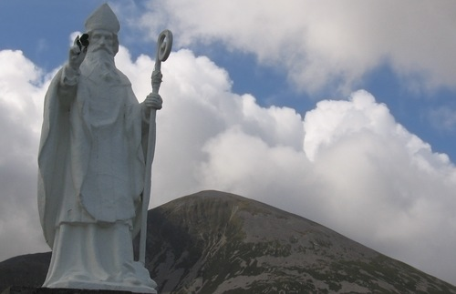 A statue of Saint Patrick stands in front of a mountain named after the saint in Ireland