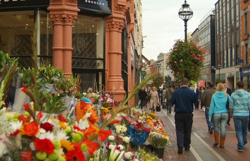 Pedestrians stroll past shops and flowers for sale on Grafton Street in Dublin
