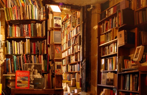 Books reach to the rafters on rickety shelves inside Shakespeare and Company, an acclaimed English-language bookstore in Paris