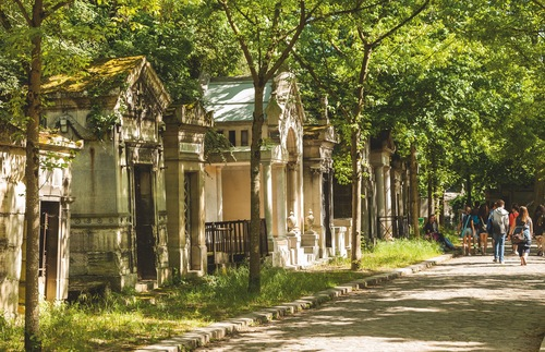 Visitors stroll past crypts along a leafy walkway in Père-Lachaise cemetery in Paris