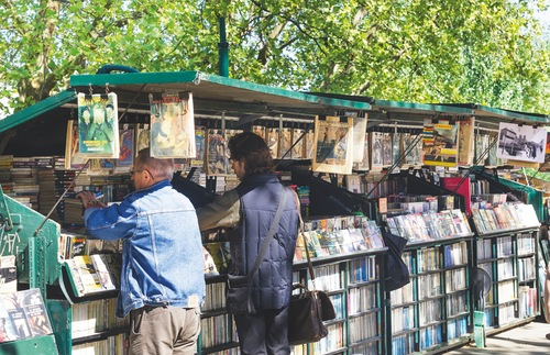 Shoppers browse the wares at a stall selling second-hand books and memorabilia along the Seine in Paris