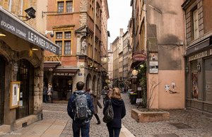 Tourists and locals walking a cobble-stoned street of Vieux Lyon with several Lyonnais bouchons, boulangeries, and restaurants