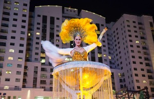 A showgirl pops out of a massive champagne flute in Las Vegas