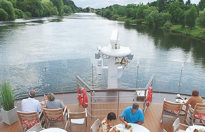 Diners enjoy a meal on deck a Viking longship during a European river cruise