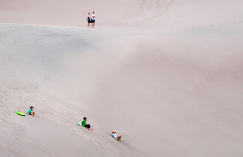 Children sledding down the massive sand dunes at Great Sand Dunes national park