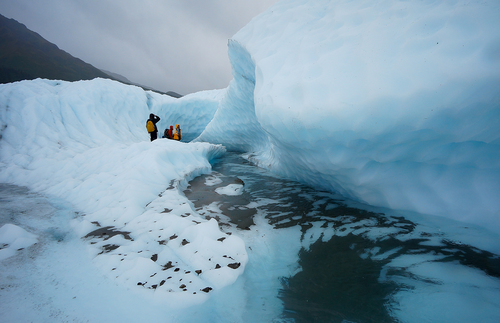 Hikers exploring a massive glacier at Wrangell-St. Elias National Park