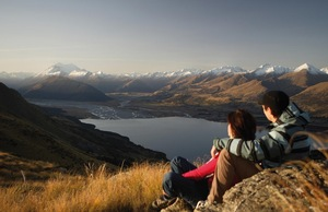 Two hikers overlook Lake Wakatipu and the surrounding snow-capped mountains in Queenstown, New Zealand