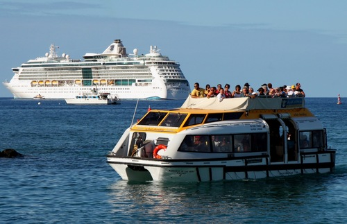 A small ship tenders passengers to shore from a big cruise ship
