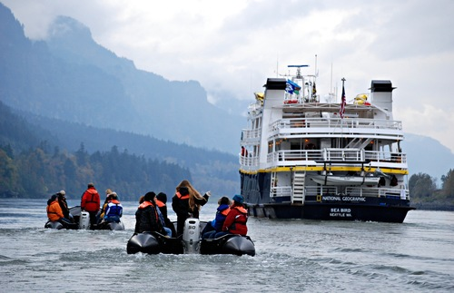 A Lindblad expeditions boat with people in zodiacs.