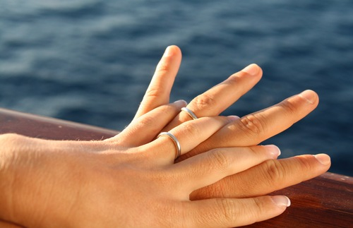 Hands with wedding rings on the railing of a ship
