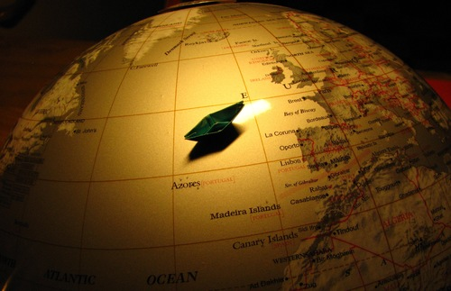 A globe with a small paper boat on it.