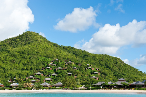 27 wooden suites on a verdant hillside are facing a white-sand beach and turquoise water.