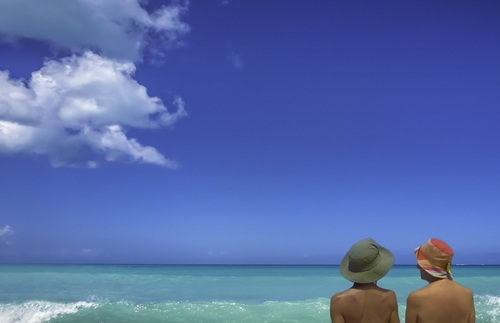 Two people in the water at Eden Beach, Antigua, a nude beach. Only their bare backs are visible.