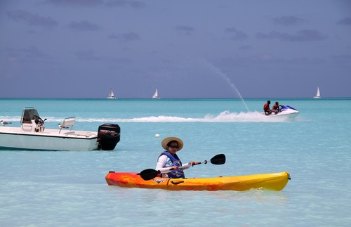 A woman kayaking in open water at Jolly Beach, Antigua. Behind her are an empty speedboat, two boys on a jet ski, and three sailboats in the distance.