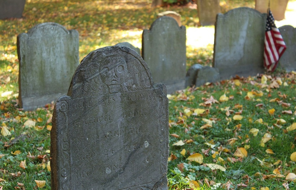 Puritan-designed gravestone with a winged death's head etched into it.