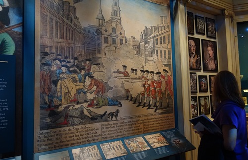 A woman gazes at a blown up poster depicting the Boston Massacre at the Museum of the American Revolution