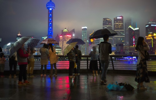 A rainy night in Shanghai. People with umbrellas look at the lit up buildings for the Bund.