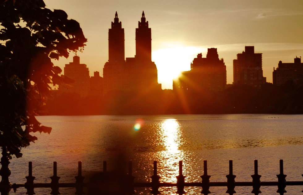 The sun sets over the reservoir in Central Park, New York City