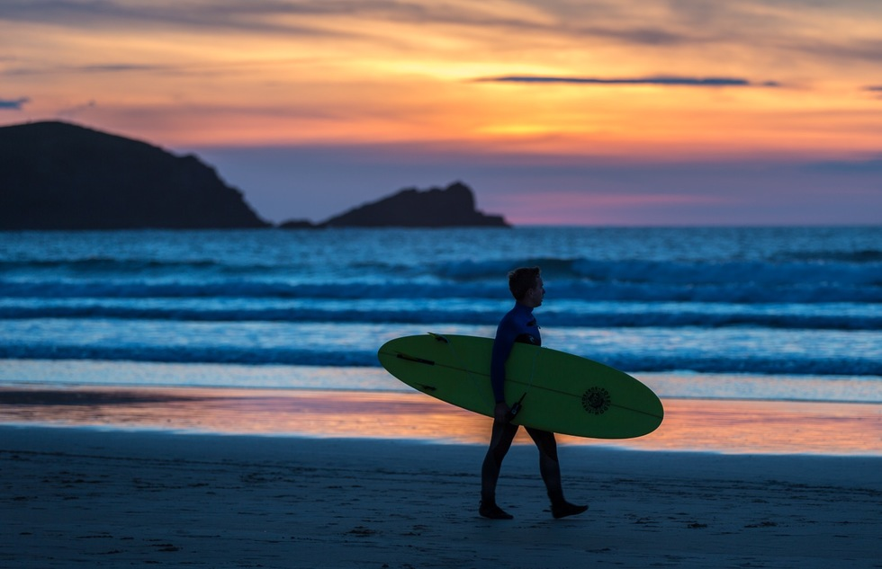 A surfer on a beach in Newquay in Cornwall, England