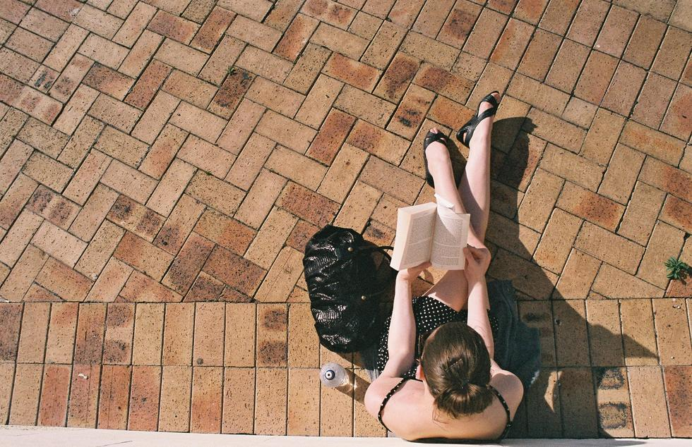 A woman sits to read a book in the sun.