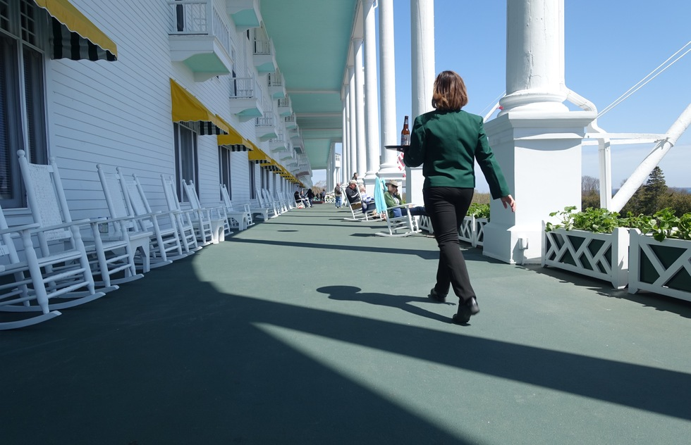 A waiter walks along the Grand Hotel's porch in Mackinac Island, Michigan