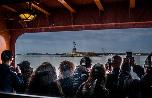 Tourists aboard the Staten Island Ferry take photos of the Statue of Liberty