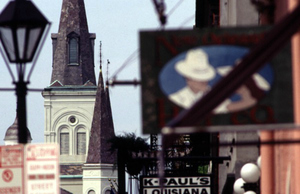 A raised level street view captures the old-fashion intricacy of the New Orlean's French Quarter. Behind the old black lamp post and hanging restaurant sign, lies the towering steeple of an old white church.