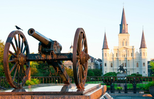 A bronze canon guards the famed Jackson Square of New Orleans French Quarter. In the background rises St. Louis Cathedral—a beautiful building standing like a Disney castle.