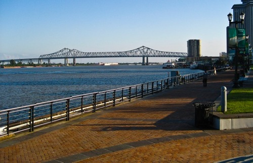 A smooth brown promenade winds down along the rolling Mississippi, forming the Moon Walk of Woldenberg Park. The view includes the buildings along the New Orleans river and a distant bridge.