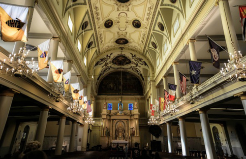 The breath-taking interior of the St. Louis Cathedral features a beautiful vaulted ceiling adorned with small paintings. Balconies run along both sides of the inside with various flags hanging off them.