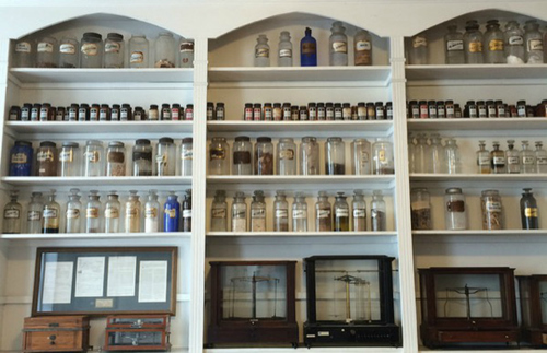 This photo features a series of shelves filled with old-fashioned, glass medical bottles. Below are well-preserved balance scales in their cases.
