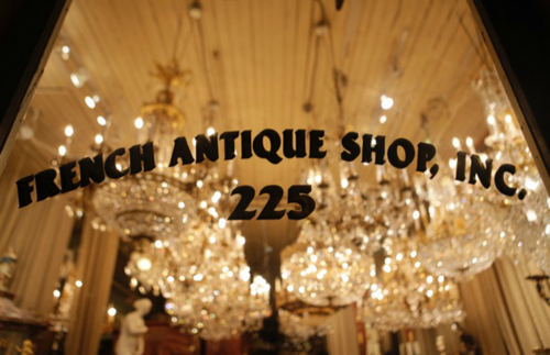 A clean glass window store front is illuminated by the dazzling chandeliers, showing the etched black lettering—French Antique Shop.