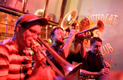 A row of musicians blast various horns at the Spotted Cat Music Club.