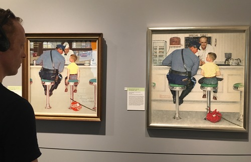 A viewer looks at two version of Rockwell's iconic painting of a policeman and a young runaway