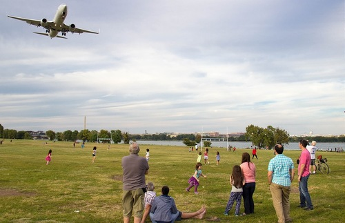 Plane flies over kids playing in park