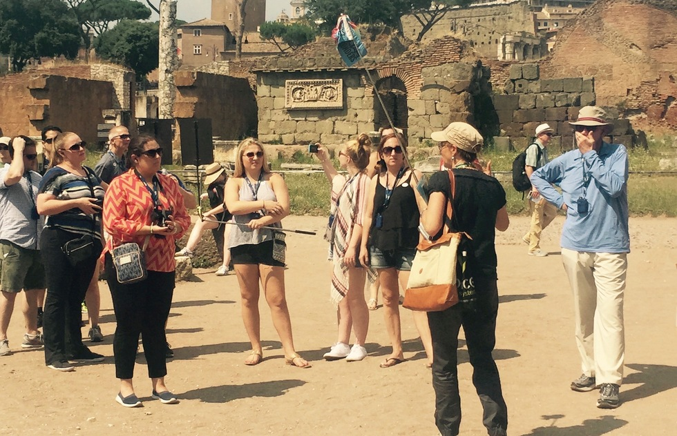 A tour group listens to a guide among the ruins of Rome.
