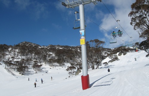 Skiers ride under lift at Perisher