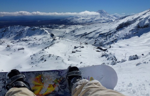 Snowboarder looks down into the valley